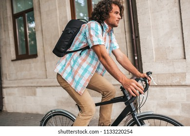 side view of young hipster male in casual clothes with backpack, looking away while leaning on his bycicle outdoors in the city street. Student riding to college. People, lifestyle, business concept.