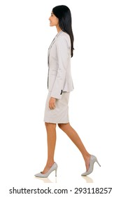 side view of young indian businesswoman walking on white background