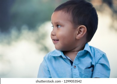 A side view of a young kid that is concentrated and looking at something at a distance, with a cute smile.
