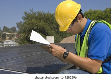 Side view of young maintenance worker making notes near solar panels on rooftop