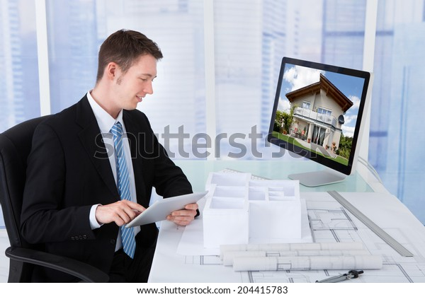 Side view of young male architect browsing property on computer in office