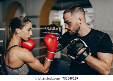 side view of young male and female boxers training on boxing ring