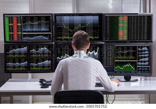Zijaanzicht Van Een Jonge Mannelijke Stock Market Broker Analyseren Grafieken Op Meerdere Computer Schermen