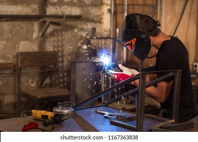 Side view of young male welder, wearing in black t shirt, construction gloves and welding mask, hardworking and welding with welding machine metal in workshop. Much equipment laying on work table.