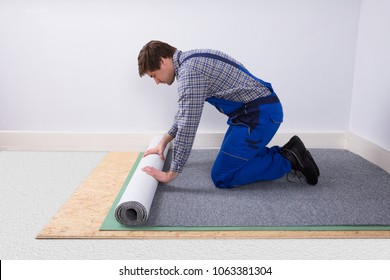 Side View Of A Young Male Worker In Overalls Installing Carpet