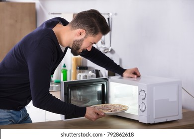 Side View Of A Young Man Baking Pizza In Microwave Oven
