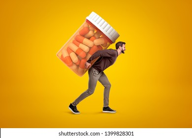 Side view of young man in casual clothes carrying big heavy-looking medicine jar on yellow background. Excessive drug use. Addicted to medication. Dietary additives.