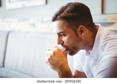 Side view of young man drinking cup of coffee at the cafe