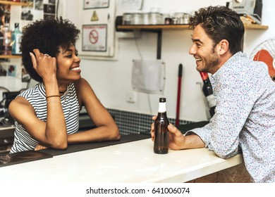 Side view of young man drinking beer in bar and flirting with bartender.