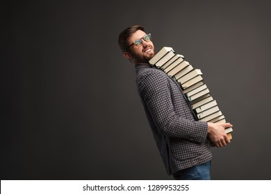 Side view of young man in glasses and checkered shirt looking at camera and carrying heavy pile of books while standing on gray background