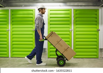 Side view of young man in overalls walking with cart with boxes along the corridor of warehouse