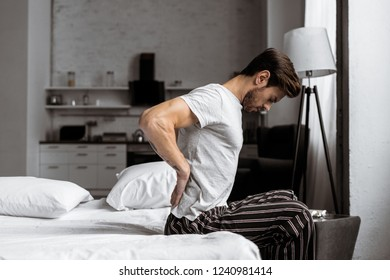 side view of young man in pajamas suffering from backache while sitting on bed in the morning
