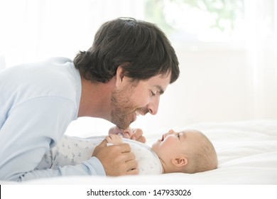 Side view of a young man playing with his little baby in bed