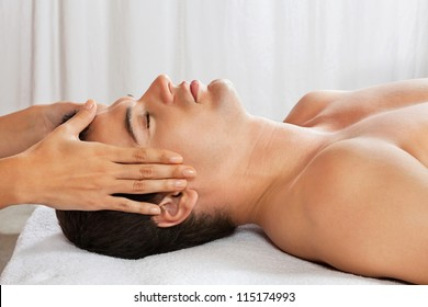 Side view of young man receiving head massage at health spa