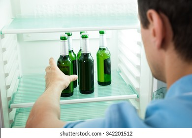 Side view of young man removing beer bottle from refrigerator at home