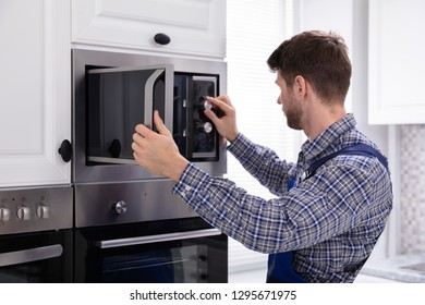 Side View Of Young Man Repairing Microwave Oven In Kitchen