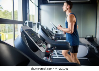 Side view of young man running on treadmill in modern gym by window, focus in foreground on row of machines