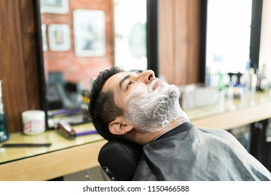 Side view of young man with shaving foam on face in salon