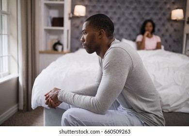 Side view of young man siting while woman resting on bed at home
