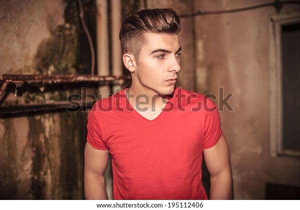 side view of a young man standing in a dirty place of an old building