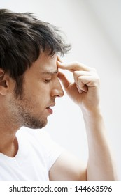 Side view of young man suffering from headache