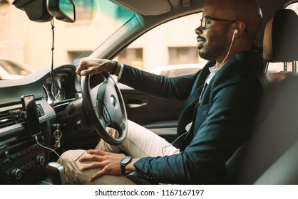 Side view of young man in suit listening music while driving car. African businessman driving a vehicle to office.
