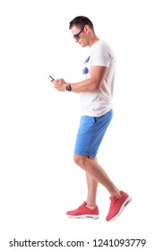 Side view of young man in summer clothes walking and using mobile phone. Full body isolated on white background.