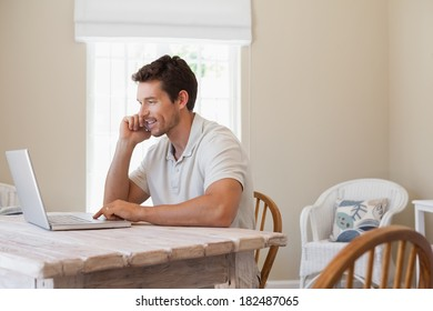 Side view of a young man using mobile phone and laptop at home