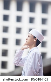Side view of Young man wearing Islamic clothes while doing azan in the mosque