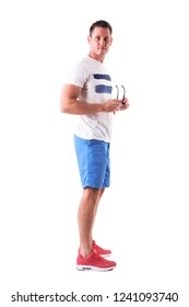 Side view of young man wearing t-shirt and shots holding sunglasses looking at camera. Full body isolated on white background.