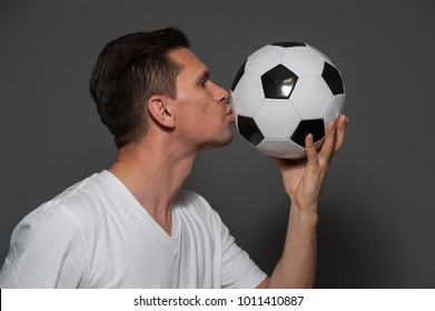 Side view of young man in a white T-shirt football fan or player kissing ball on gray background