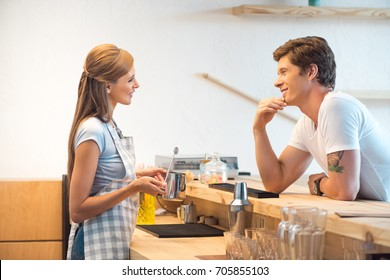side view of young man and woman flirting and smiling each other while working n cafe