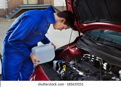 Side view of young mechanic pouring antifreeze into windscreen water tank on street