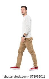 Side view of young modern stylish man walking and looking at camera. Full body length portrait isolated over white studio background.