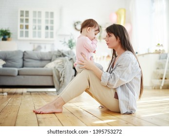 Side view of young mother sitting on floor at home and talking to her baby daughter sucking her thumb. Mom trying to break thumb-sucking habit