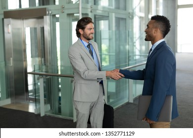 Side view of young multi-ethnic businessmen shaking hands with each other in the modern corridor at office. They are smiling