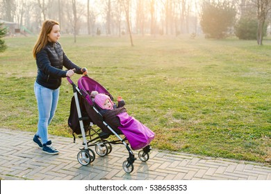 Side view of young mum walking in park while pushing her toddler sitting in a stroller
