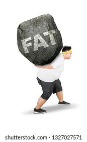 Side view of young obese man carrying fat word in a rock while walking in the studio