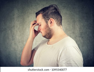 Side view of young overweight man thinking on solution while rubbing forehead.