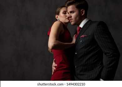 side view of a young passionate couple embracing strongly each other with a seductive look on their face on gray studio background