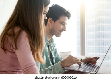 Side view of young people shopping online via laptop computer, e-commerce, internet banking, financial operations. Man holding credit card, making payments, buying, woman choosing, booking, ordering