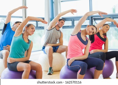 Side view of young people sitting on exercise balls and stretching out hands in the bright gym
