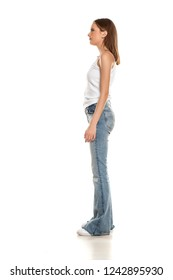 Side view of young pretty woman posing in bell bottom jeans on white background