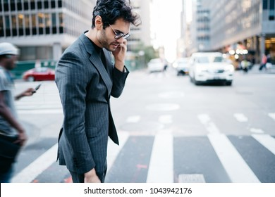Side view of young proud CEO dressed in stylish formal apparel crossing street on zebra in downtown of metropolis while talking on smartphone.Executive manager communicating on telephone in New York