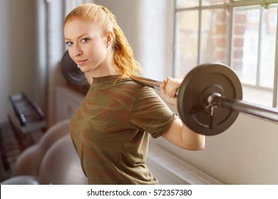 Side view of young red-haired girl in brown T-shirt standing next to window, holding bar bell behind her back and looking at camera