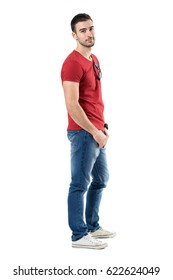 Side view of young relaxed casual man in red t-shirt and jeans looking at camera. Full body length portrait isolated over white studio background.