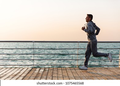 Side view of young running sportsman, during workout on quay, near the ocean. Full length.