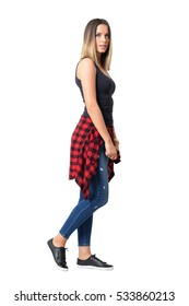 Side view of young serious woman walking with shirt around waist looking at camera.  Full body length standing portrait isolated over white background.