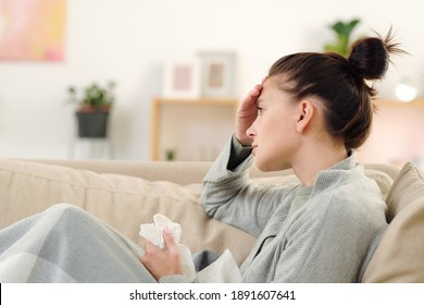 Side view of young sick woman with crumpled handkerchief sitting on couch under blanket, touching her forehead and suffering from headache