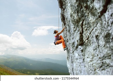 side view of young slim woman rock climber in bright orange pants climbing on the cliff against a blue sky. girl climbs on a vertical flat rocky wall and making hard move. Copy space